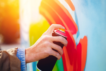 Photo pour Artist graffiti with a balloon paint in his hands draws on the wall - image libre de droit