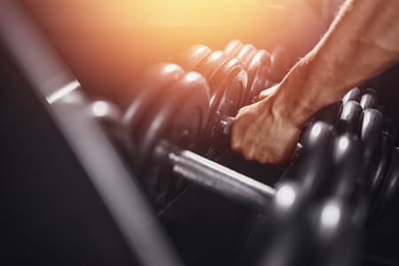Foto de Dumbbell. Close-up man grabs a heavy dumbbell in the gym with his hand. Concept lifting, fitness. - Imagen libre de derechos