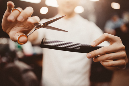 Foto für Barber shop. Close-up of barber holds clip-on hair clipper barbershop - Lizenzfreies Bild
