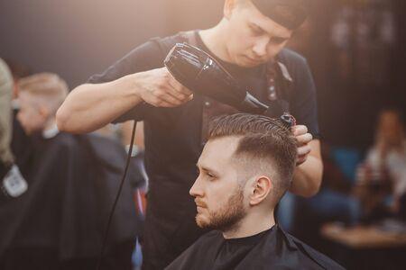 Foto für Barber shop. Master stacks hair of men hairdryer in barbershop, hairdresser makes hairstyle for young man - Lizenzfreies Bild