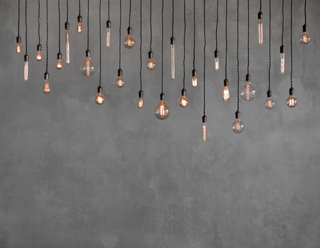 Foto de Edison retro lamp Incandescent bulbs on gray plaster wall background in loft. Concept Vintage style. Copy space - Imagen libre de derechos