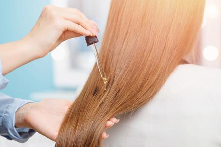 Foto de Master woman applying oil mask to hair tips in salon. Concept beauty and haircare - Imagen libre de derechos