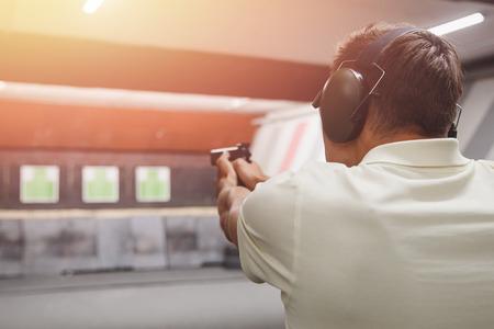 Photo pour Man shoots pistol in noise protection headphones. Shooting range gun. - image libre de droit