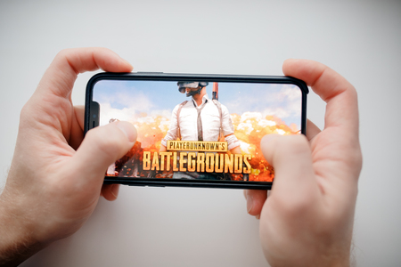 Photo pour Moscow, Russia - January 1, 2019 : Man holding smartphone with Player Unknown Battleground PUBG online shooting gaming. - image libre de droit