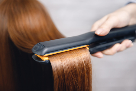 Photo pour Girl does straightening of long shiny red hair with iron in beauty salon - image libre de droit