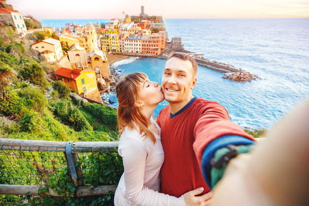 Photo pour Tourists happy couple taking selfie photo of Vernazza, national park Cinque Terre, Liguria, Italy, Europe. Concept travel. - image libre de droit