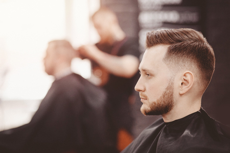 Photo pour Barbershop banner. Man in barber chair, hairdresser styling his hair - image libre de droit