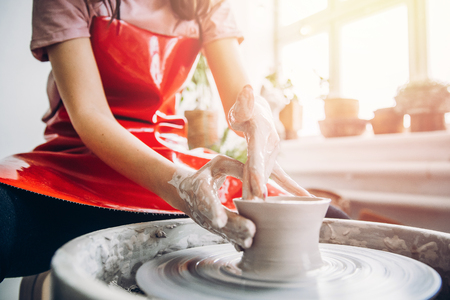 Photo pour Young woman in red apron works behind potter wheel with length, making handmade plate. Concept of concentration, creativity hand made. - image libre de droit