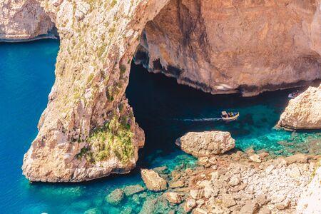 Photo pour Blue Grotto in Malta. Pleasure boat with tourists runs. Natural arch window in rock. - image libre de droit