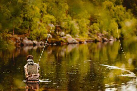Foto de Fisherman using rod fly fishing in river morning sunrise splashing water. - Imagen libre de derechos