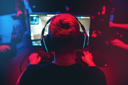 Photo for Professional gamer playing online games tournaments pc computer with headphones, Blurred red and blue background - Royalty Free Image