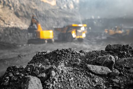 Photo pour Coal open pit mine. In background blurred loading anthracite minerals excavator into large yellow truck. - image libre de droit