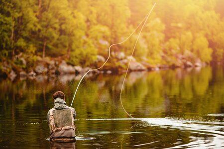 Photo pour Fisherman using rod fly fishing in mountain river autumn splashing water. - image libre de droit