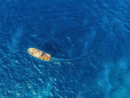 Photo pour Fishing boat in blue sea water, fishermen set nets for fish. Aerial top view. - image libre de droit