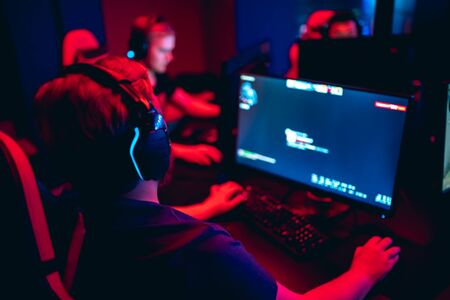 Photo pour Blurred background professional gamer playing tournaments online games computer with headphones, red and blue - image libre de droit