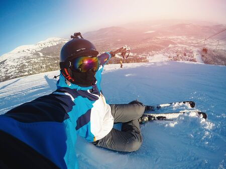 Photo pour Winter extreme sport with selfie action camera. Man rides on slopes skis in protective helmet - image libre de droit