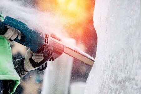 Photo pour Ice sculpture carving man use chainsaw cut frozen winter. - image libre de droit