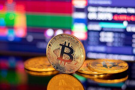 Foto de Gold Bitcoin crypto currency on background of dawn chart diagram depreciation - Imagen libre de derechos