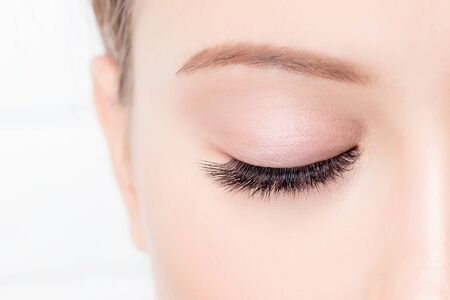 Photo pour Closed female eye with beautiful makeup and long lashes on white background. Concept eyelashes extensions procedure. - image libre de droit