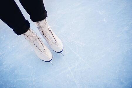 Foto de Woman standing on ice in white figure skates, snow flakes sunset. Top view. - Imagen libre de derechos