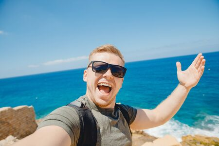 Photo pour Happy traveler man taking selfie photo in sunglasses on background of bruise sea with backpack. Travel concept - image libre de droit