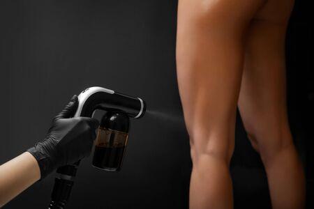 Foto de Cosmetology professional applying liquid tan spray on woman skin with aerograph on black background - Imagen libre de derechos