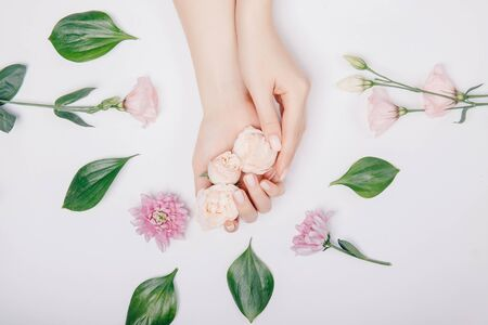 Photo pour Close-up beautiful sophisticated female hands with pink flowers on white background. Concept hand care, anti-wrinkles, anti-aging cream, spa - image libre de droit