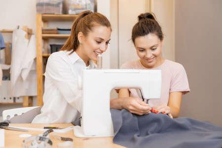 Photo pour Fashion designers clothes young girls discuss color and shape, dress sewing style - image libre de droit