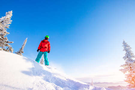 Photo pour Snowboarder jumping through air with deep blue sky in background, Freeride winter forest - image libre de droit