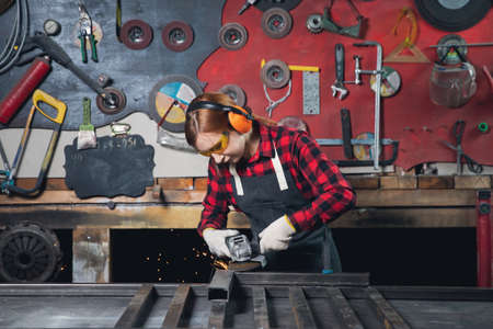 Photo for Worker girl with electric saw wheel grinding on steel structure in factory, light spark - Royalty Free Image