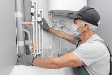 Photo pour Male plumber in medical mask checks pipes for central hot and cold water supply of apartment - image libre de droit