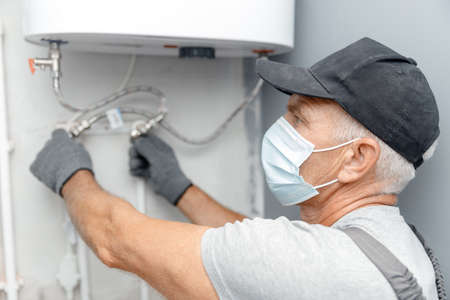 Photo for Plumber man in medical mask installing boiler water heater in bathroom - Royalty Free Image