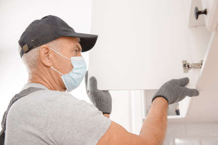 Photo pour Kitchen installation, worker in medical mask assembling furniture white carved cabinet front - image libre de droit
