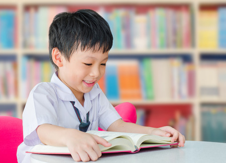 Photo for Asian boy student in uniform reading book in school library - Royalty Free Image
