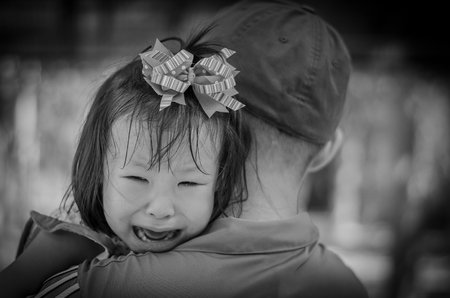 Little girl crying between stranger holding ,black and white color