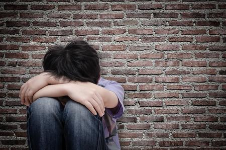 Foto de Little sad boy sitting on floor over old wall - Imagen libre de derechos
