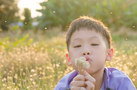 Asian child blowing away flower in spring