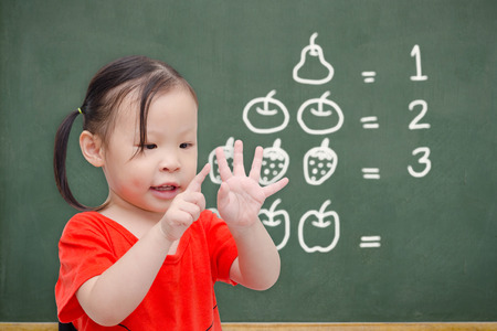 Photo pour Little asian girl counting her finger in font of chalkboard - image libre de droit