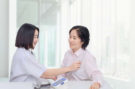 Asian doctor checking patient heart by stethoscope