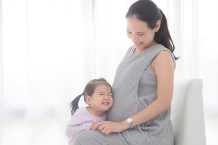 Photo for Little asian girl hugging her pregnant mother belly and smiles at home - Royalty Free Image