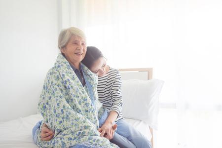 Foto de Asian daughter hugging her senior mother in bedroom at home - Imagen libre de derechos