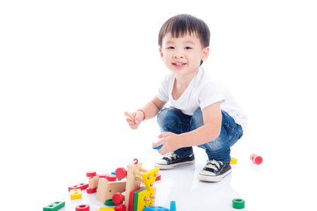 Photo pour Little asian boy playing toy on the floor over white background - image libre de droit