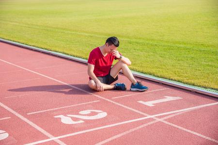 Foto de Sad asian man sitting and cry on the floor after losing in competition - Imagen libre de derechos