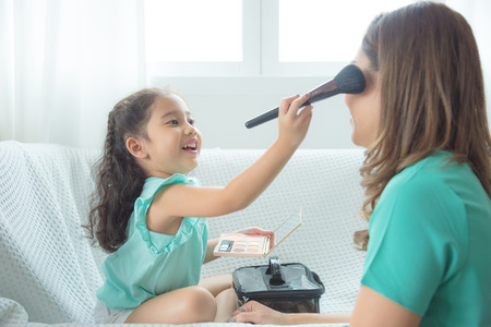 Photo pour Cute asian daughter putting makeup on her mother face at home. - image libre de droit