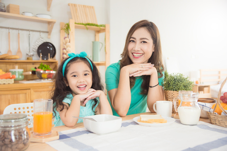 Foto de Beautiful asian mother and daughter having breakfast together at home in the morning - Imagen libre de derechos