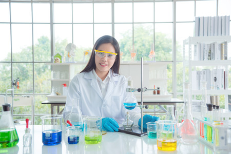 Foto de Smiling asian chemist wearing safety glasses and coat sitting in lab - Imagen libre de derechos