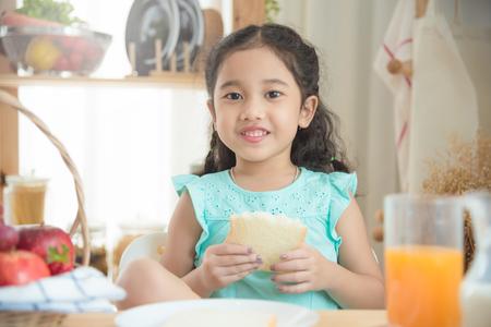 Foto de Little asian girl eating bread at breakfast table - Imagen libre de derechos