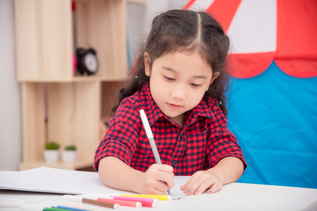 Photo pour Little asian girl drawing picture by color marker on table at home - image libre de droit