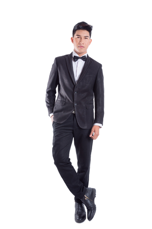 Photo pour Portrait of young asian confident man dressed in tuxedo with bow tie isolated on white background - image libre de droit