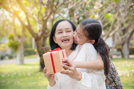 Photo pour Asian granddaughter giving birthday gift for granddaughter in the garden.Happy Asian family conception. - image libre de droit